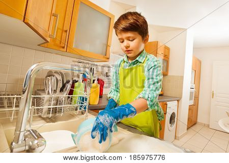 Portrait of six years old boy doing the dishes under running water in the sink in the kitchen