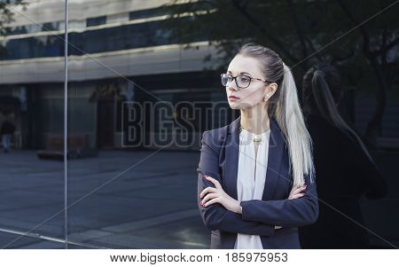 Serious young woman in suit and glasses business manager or teacher on dark background