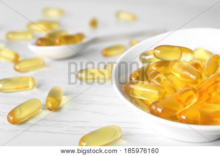 Small bowl with fish oil capsules on table