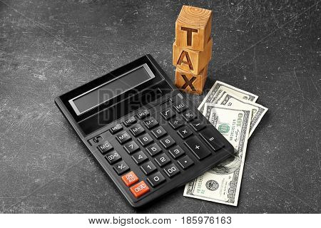Wooden blocks with word TAX, calculator and banknotes on gray background