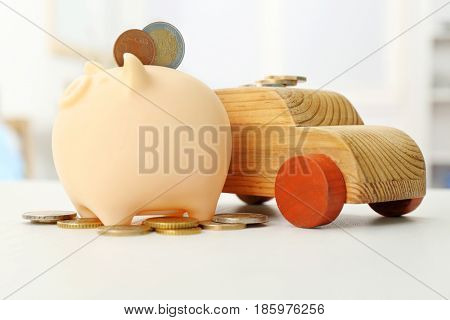 Piggy bank with coins and wooden toy car on table