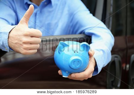 Man holding piggy bank in his new car