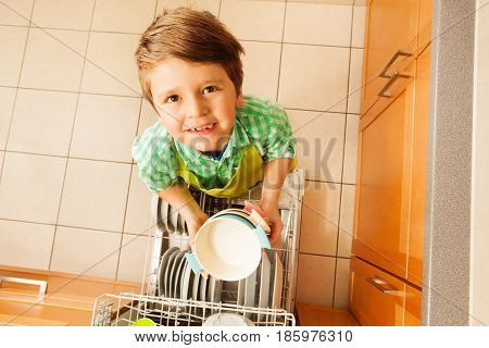 Close-up portrait of kid boy holding clean bowls standing next to dishwashing machine in the kitchen