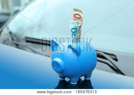 Ceramic piggy bank with banknote on hood of car