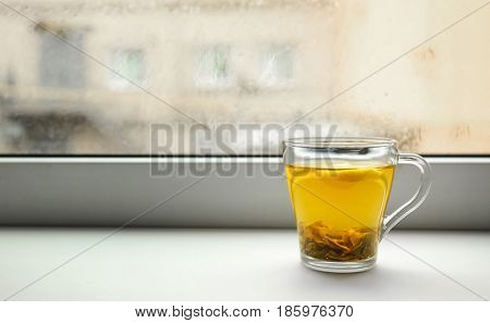 Cup of hot tea on window sill