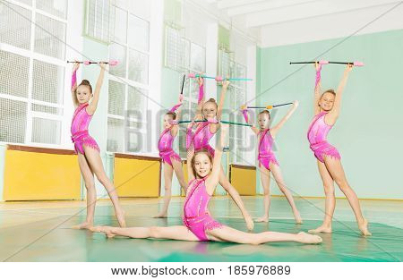 Group of six gymnast girls with juggling clubs in the gym training