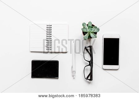 office flat lay table with mobile phone, glasses, notebook on white background top view mockup