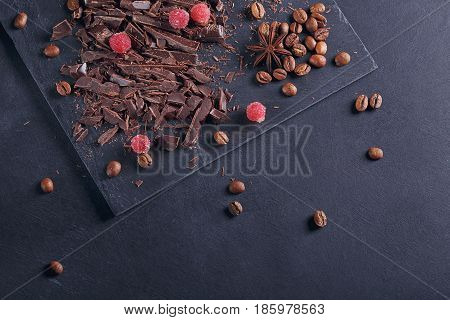 Dark chopping chocolate black roasted coffee beans red berries with spices on slate board over black textural background. Sweets concept. Top view with space for text.