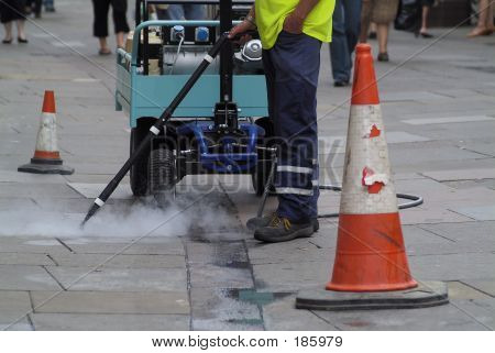 steam cleaning pavement sidewalk of gum spewed out by yobs poster