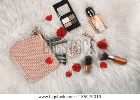 Cosmetics and perfume on furry background