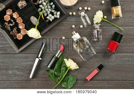 Cosmetics and perfume bottles on wooden background