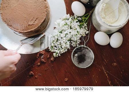 woman hands makeing cake on wooden background