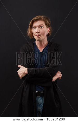 Close up of crazy nerd man making funny face, isolated on black background.
