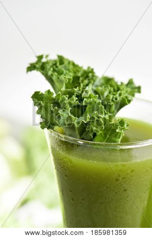 a kale smoothie served in a glass topped with a leaf of kale, on a white background