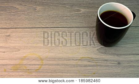 Black and white Coffee cup with coffee stain on wooden floor
