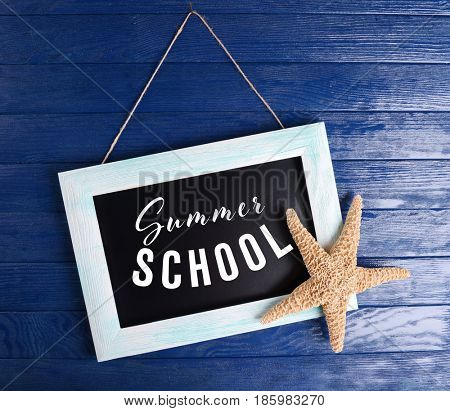 Small blackboard with text SUMMER SCHOOL hanging on wooden background