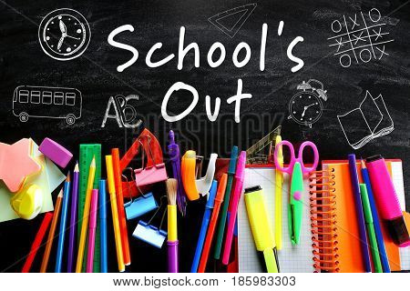 Text SCHOOL'S OUT and stationery on blackboard background