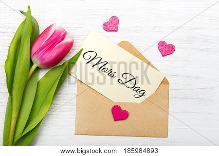 Mother's day car with Swedish words: Mother's day. Tulip and envelope on white wooden background