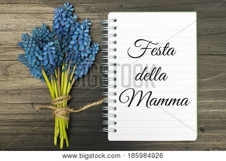 Mother's day card with Italian words: Happy mother's day. Blue flowers and notebook on a dark wooden background