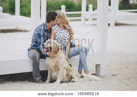 couple walking in the park with his dog girl playing with a dog ot the beach and in the park