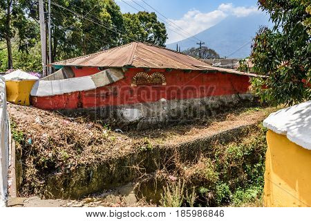 Antigua, Guatemala - March 26 2017: Red wall of house by dry riverbed with Agua volcano behind in colonial city & UNESCO World Heritage Site of Antigua, Guatemala, Central America
