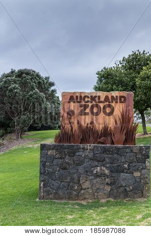 Auckland New Zealand - March 5 2017: Rustic colored welcome sign for Auckland Zoo on stone footing in Western Springs Park. Gray-blue skies and green vegetation.