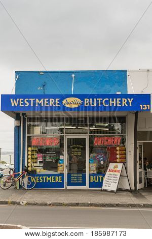 Auckland New Zealand - March 5 2017: Facade of authentic iconic butchery in the Westmere division of the city. Blue painted walls big windows advertisements for meat and a parked bike. Street scene.
