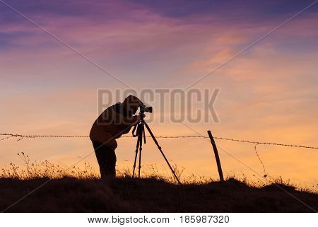 Silhouette Of Photographer With Photo Camera
