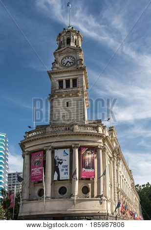 Auckland New Zealand - March 5 2017: The white stone Clock Tower of town hall with theater posters and flag. Blue sky with white clouds.