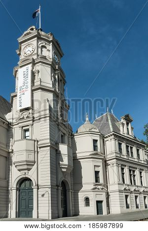 Auckland New Zealand - March 5 2017: Closeup of the gray stone clock tower and building of public Auckland Art Gallery set along the street. Blue sky.