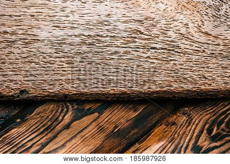 Background of textured burned pine wood with board pitted with holes