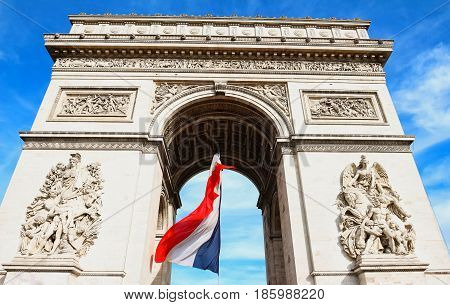 The Triumphal Arch decorated with National French flag Paris France.