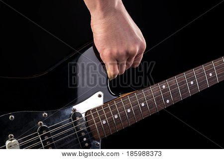 Music And Art. Electric Guitar In Hand, On A Black Isolated Background. Horizontal Frame