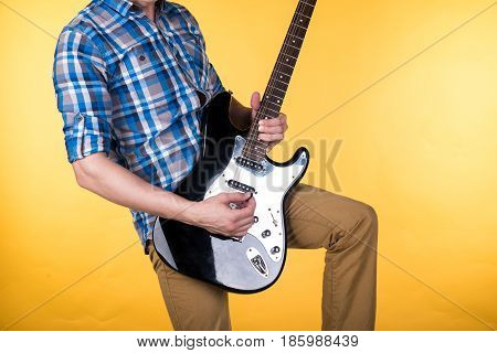 Music And Art. The Guitarist Plays The Electric Guitar On A Yellow Isolated Background. Playing Guit