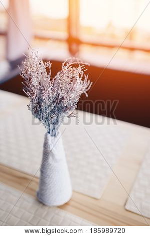 Dry flowers painted in white are in a vase on a wooden table with a glare from the sun. Concept detail of the interior of the restaurant and cafe.