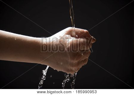 Trying to catch water in the fist, isolated on the black background