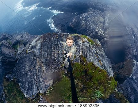 Male tourist man sitting jumping on a mountain on a  sea background. Teriberka, Murmansk region, the Kola Peninsula, Russia. action cam