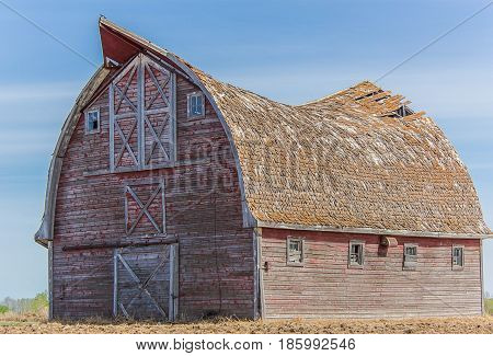 big faded red barn with a sagging roof