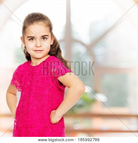 A beautiful little girl of primary school age, with long flowing hair, in a bright red dress.She is posing in front of the camera, holding hands in the ribs. Close-up.In the sports hall with mirror and a large semi-circular window.
