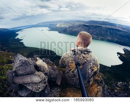tourist man stands and sits in the mountains and rocks against the background of the sea. Mountains of Khibiny, Seydozero. Murmansk Region, Kola Peninsula, Russia. action cam