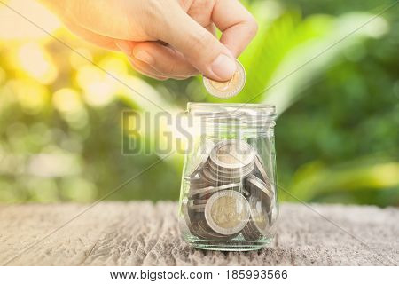 women hand putting money coin in jar. concept saving money growing business
