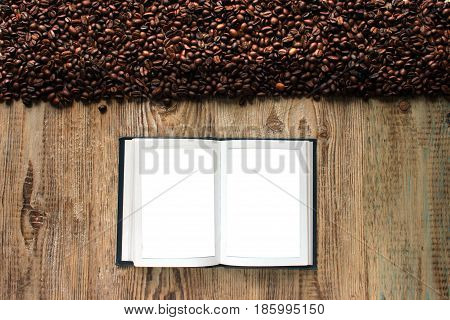 Beans of the coffee house on a wooden table, unfolded book for recipe recording