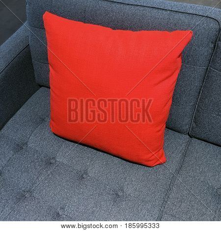 Vibrant red cushion decorating gray sofa. Modern style furniture.