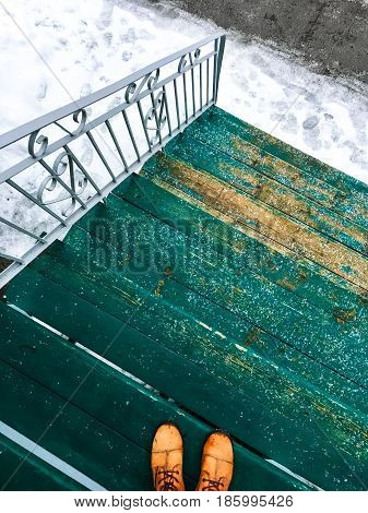 Person in orange boots standing on a green wooden staircase leading onto a winter street.