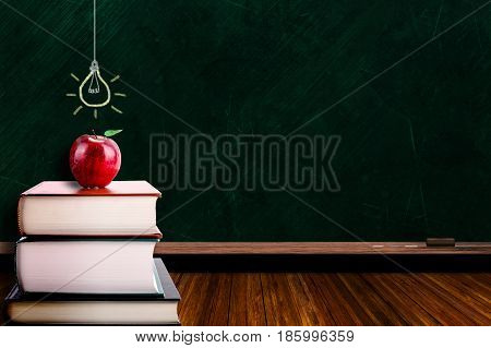Education Concept With Apple On Books And Lightbulb On Blackboard