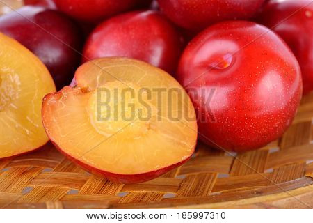 whole and half cut fresh gulf ruby plum in the bamboo basket