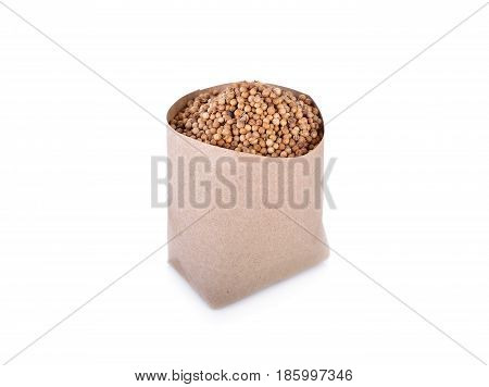 dried coriander seeds in paper bag and on white background