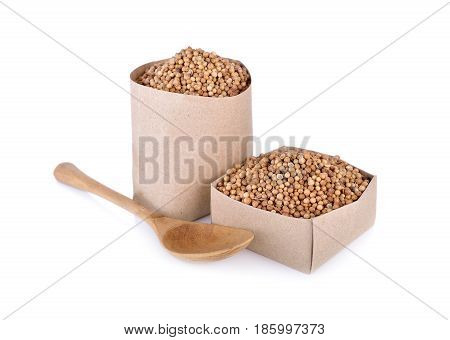 dried coriander seeds in paper bag and box on white background