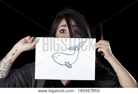 Quito, Ecuador - May 09, 2017: Anxious teenager drawing a whale over a sheet of paper, social suicide concept as a sociology metaphor for crowd or herd mentality and group decisions resulting in violence or population death as a network of connected.