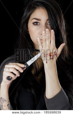 Quito, Ecuador - May 09, 2017: Close up of an anxious teenager in day 1 blue whale challenge writing the word f57 in her hand with a knife, social suicide concept as a sociology metaphor for crowd or herd mentality and group decisions resulting in violenc
